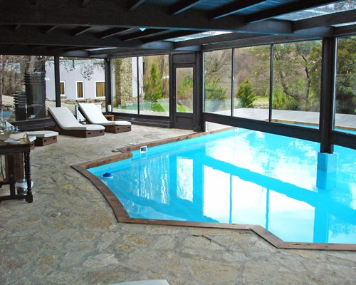 An indoor swimming pool with chaise lounge chairs and outside view.