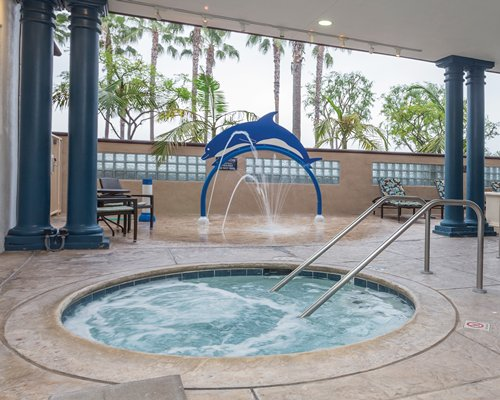 A view of an indoor hot tub with water fountain and patio furniture.