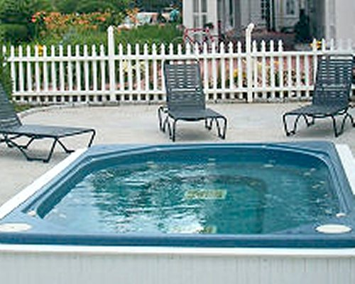 An outdoor hot tub with chaise lounge chairs.