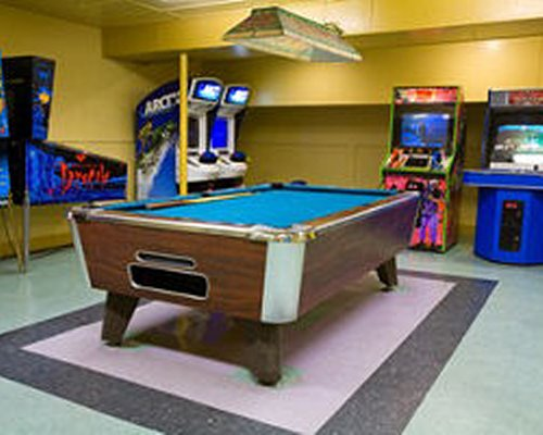 An indoor recreation area with pool table and arcade games.