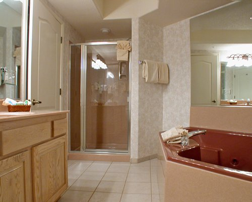 A bathroom with stand up shower bathtub and single sink vanity.