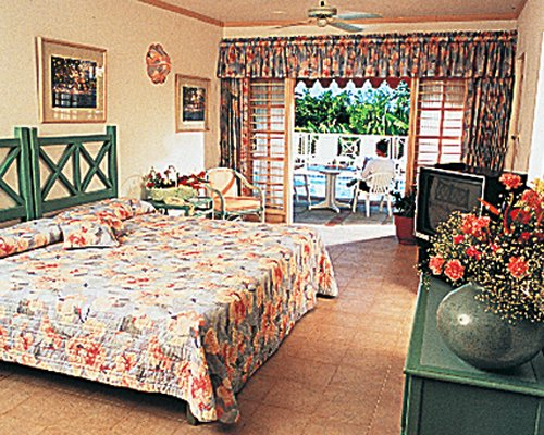 A well furnished bedroom with a television and balcony.