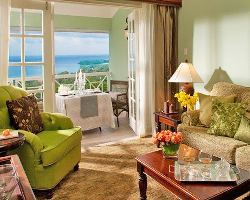 A well furnished living room with a balcony and the beach view.