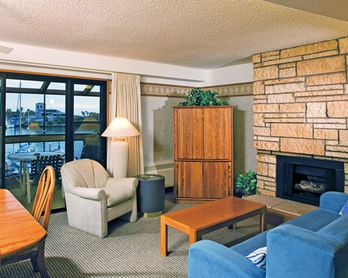 A well furnished living room with fireplace dining area and patio.