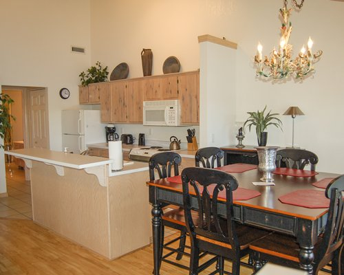 A well equipped kitchen with wooden dining area.