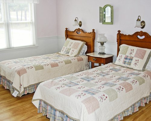 A well furnished bedroom with two twin beds with an outside view.