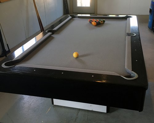 An indoor recreation room with a pool table.