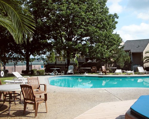 An outdoor swimming pool with chaise lounge chairs alongside patio furniture and resort units.