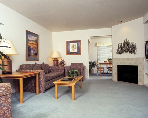A well furnished living room with sofa television and a fireplace alongside the dining area.