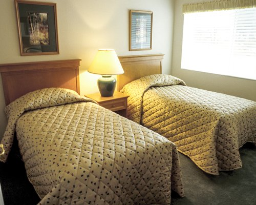 A well furnished bedroom with two twin beds and a lamp.