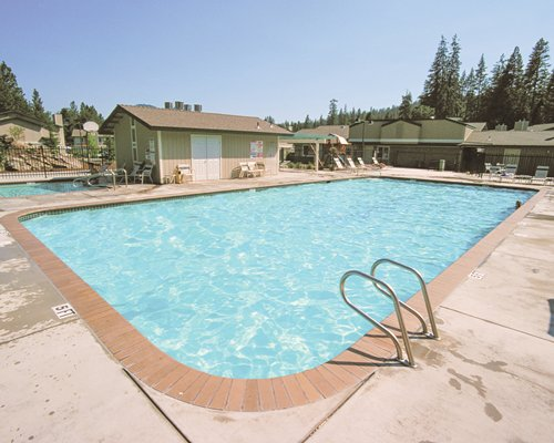 An outdoor swimming pool and kiddie pool with chaise lounge chairs alongside the resort unit.