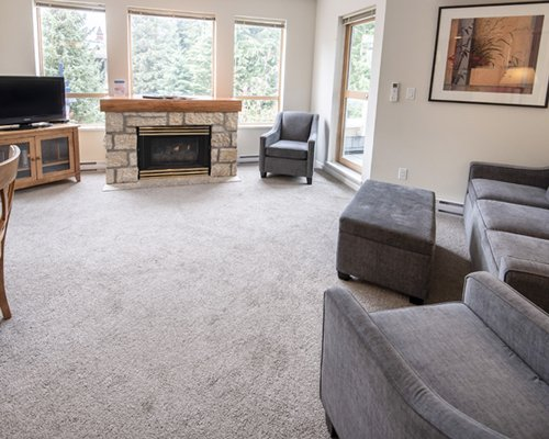 A well furnished living room with a television fireplace and outside view.