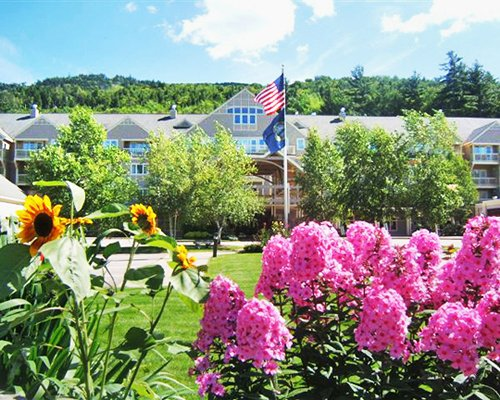 A scenic exterior view of Grand Summit Resort Hotel with flowering shrubs.