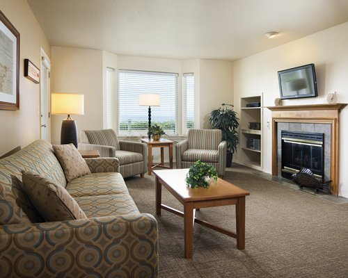A well furnished living room with fireplace television and outside view.