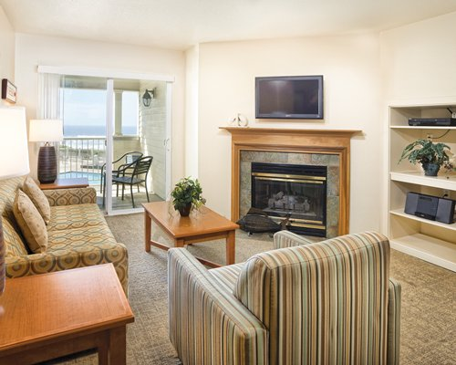 A well furnished living room with a television and fireplace alongside the balcony.