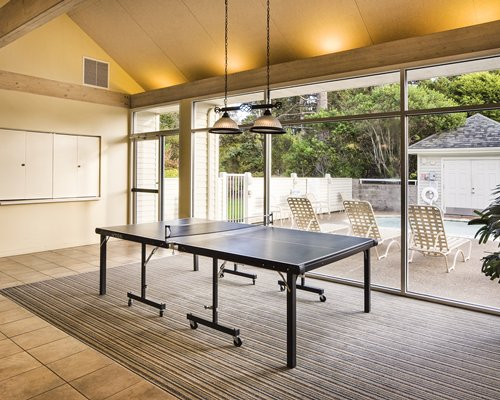 An indoor recreation room with ping pong table alongside an outdoor hot tub with chaise lounge chairs.