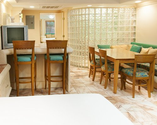 A well furnished dining room alongside a breakfast bar.