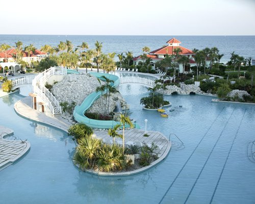 A large outdoor swimming pool with water slides surrounded by trees alongside the resort.