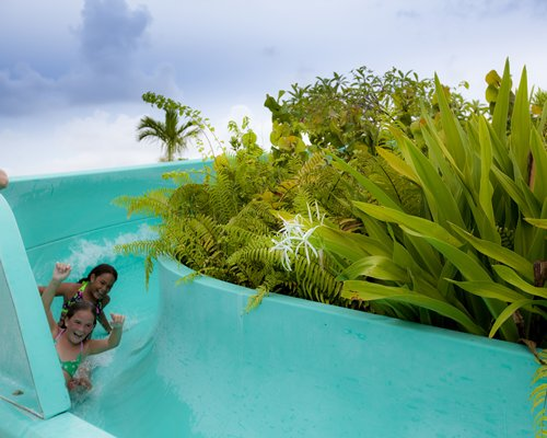 A view of two kids enjoying on a waterslide.