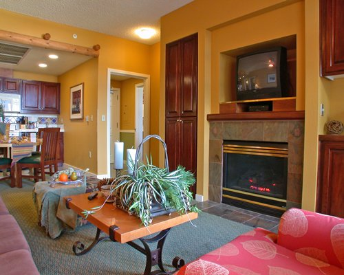 A well furnished living room with television and a fire at the fireplace alongside dining area.