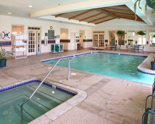 Indoor swimming pool and hot tub with patio furniture.