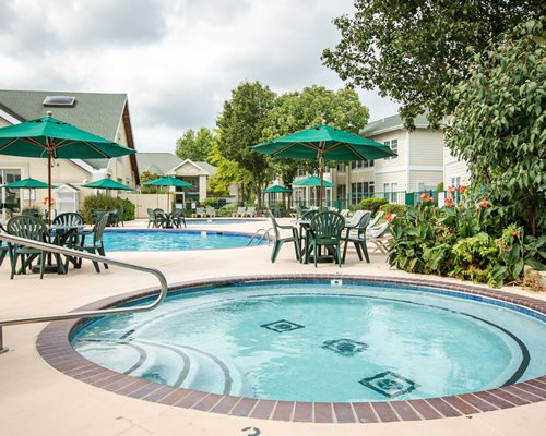 An indoor swimming pool with basketball setup chaise lounge chairs patio table sunshade and outside view.