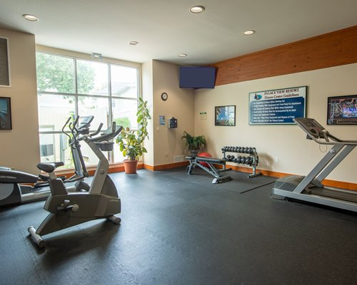 An outdoor swimming pool with chaise lounge chairs and patio furniture surrounded by trees.