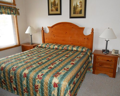 A well furnished bedroom with a king bed and an outside view.
