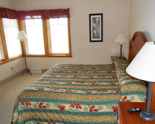 A well furnished bedroom with multiple king bed and lamp.
