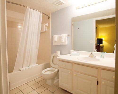 A bathroom with a toilet shower stall sink and a vanity.