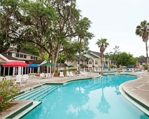 A large outdoor swimming pool with chaise lounge chairs alongside multiple resort units.