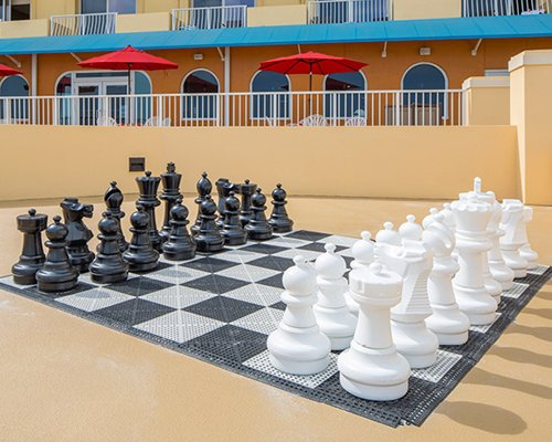 Outdoor recreation area with giant chess alongside multiple balconies with sunshades.