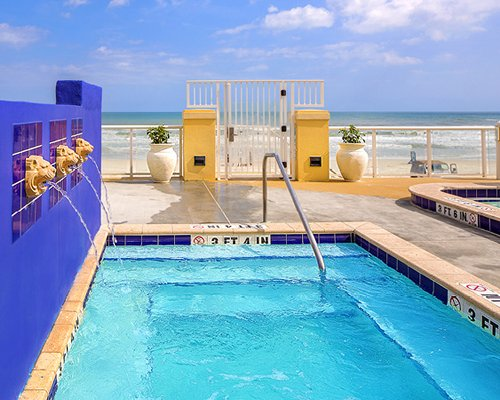 An outdoor swimming pool with water features and the beach view.