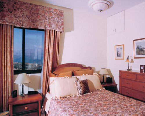 A well furnished bedroom with double bed and an outside view.