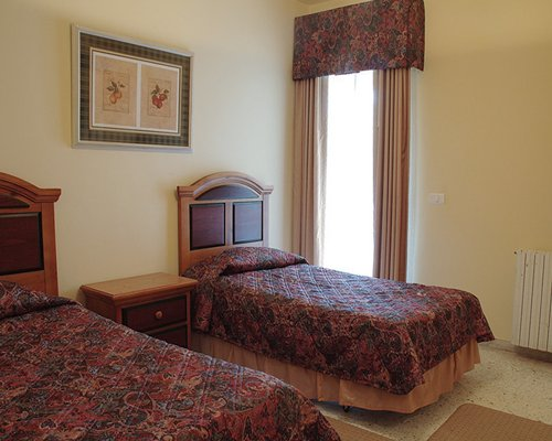A well furnished bedroom with two double beds and an outside view.