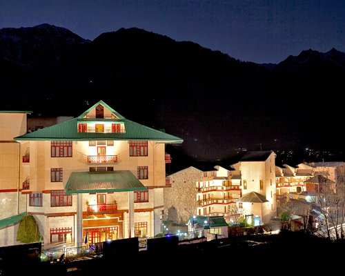 Exterior view of the Sterling Manali resort at night.