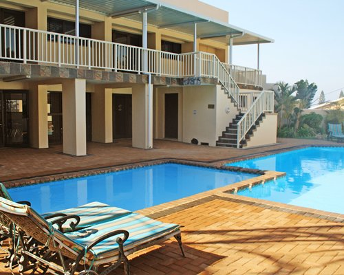 View of two outdoor swimming pool with chaise lounge chairs alongside multi story resort units.