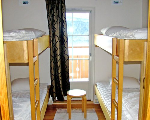 A well furnished bedroom with bunk beds and a balcony.