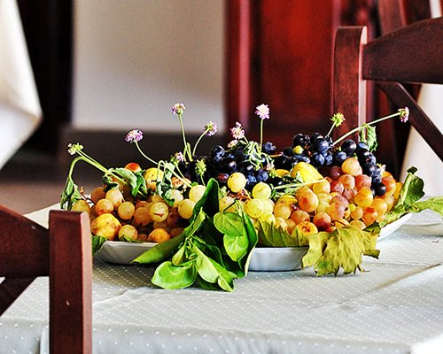 A view of fruits kept in a wooden dining table.