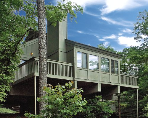 Exterior view of a unit with balcony at Petit Crest Villas surrounded by wooded area.