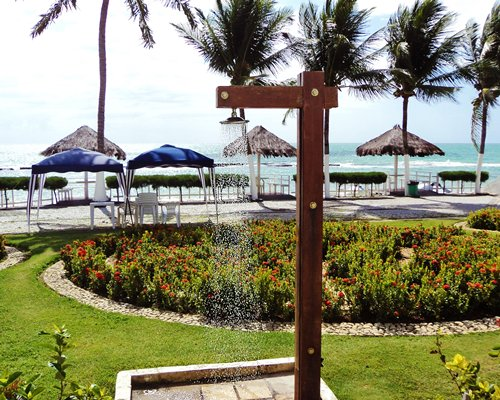An outdoor shower alongside the beach with thatched sunshades and palm trees.
