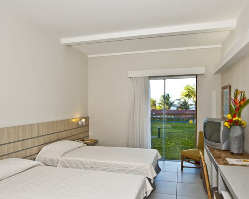 A well furnished with two twin beds television and outside view.