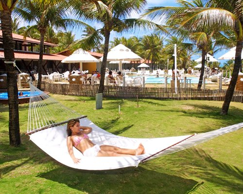 A woman in a hammock alongside an outdoor swimming pool with sunshades and palm trees.