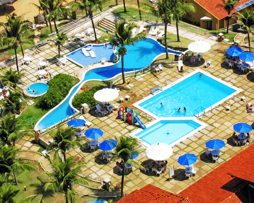 An aerial view of two large swimming pool with sunshades and.