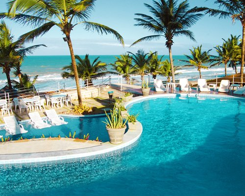 A large outdoor swimming pool with chaise lounge chairs potted plants and trees alongside the beach.