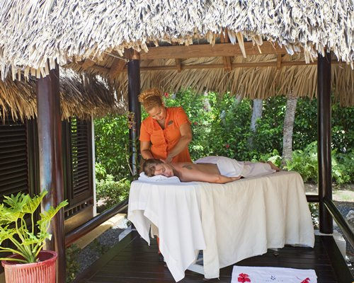 A women having body massage at the thatched covered spa.