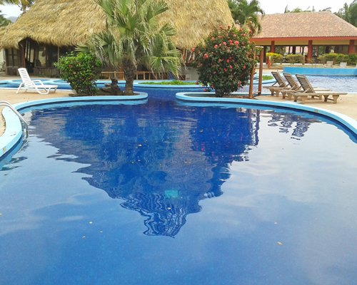 Large outdoor swimming pool with chaise lounge chairs and thatched covered pool side bar.