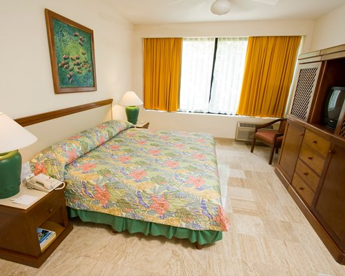 A well furnished bedroom with a king bed and television.