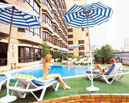 An outdoor swimming pool with sunshades and chaise lounge chairs alongside the resort.