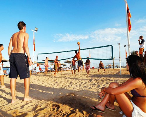 View of people playing volley ball at the beach.